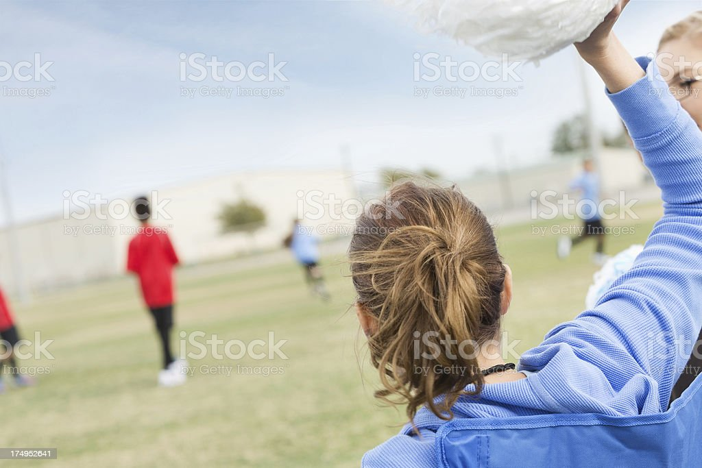 Soccer mom waving pompoms, cheering for kids during game stock photo