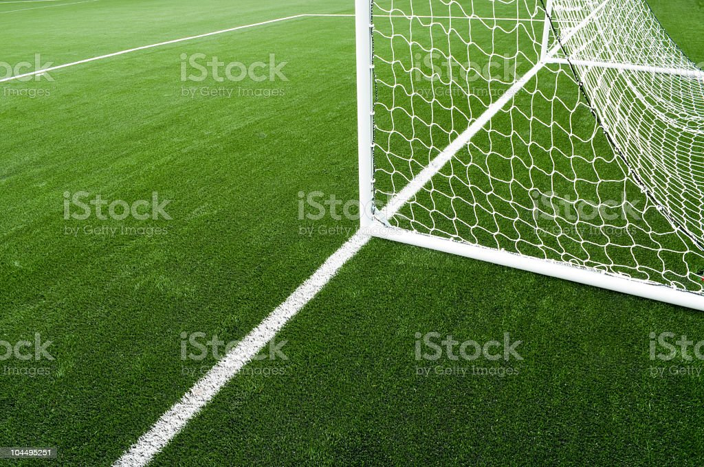 Soccer net and field on bright green artificial turf stock photo