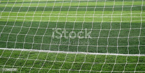 istock Soccer net  field on bright green artificial turf 1129632261