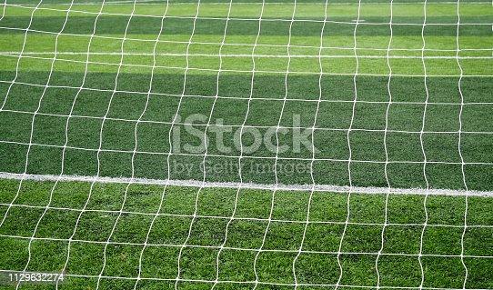 istock Soccer net  field on bright green artificial turf 1129632274