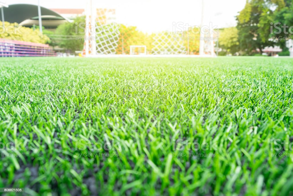 Soccer or Football artificial green grass field with empty player and sunset light for background. stock photo