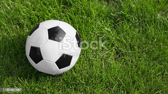 Soccer or football ball on ground. Space for text on the right side of the image