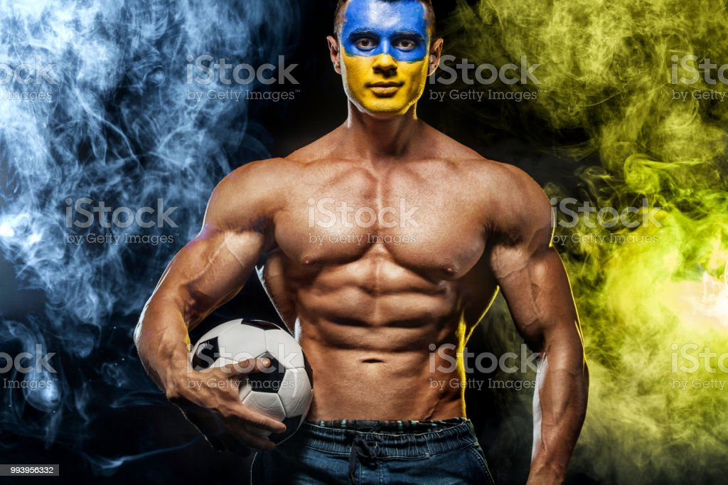 Soccer or football, fan with bodyart on face - flag of Ukraine. stock photo