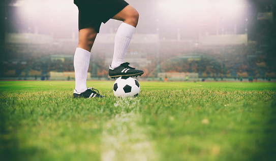 istock soccer or football player standing with ball on the field for Kick the soccer ball soft focus and selective focus on grass 824613042