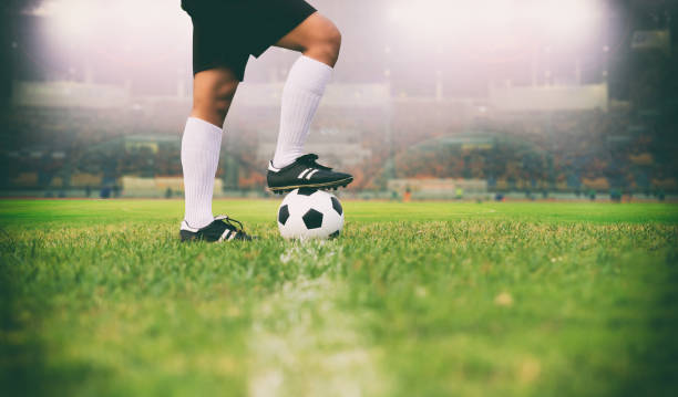 soccer or football player standing with ball on the field for kick the soccer ball soft focus and selective focus on grass - soccer stock photos and pictures