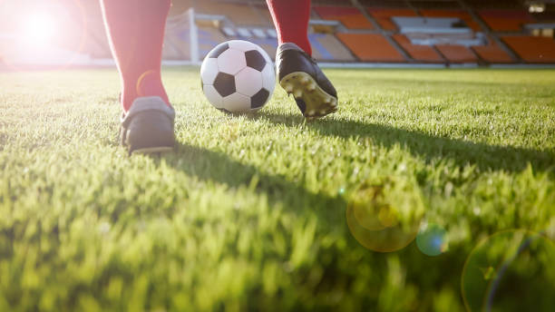 soccer or football player standing with ball on the field for kick the soccer ball at football stadium - soccer ball stock photos and pictures