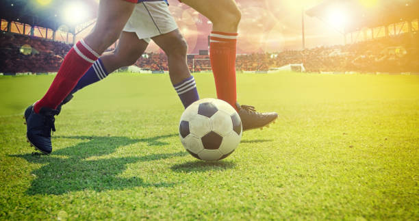 soccer or football player standing with ball on the field for Kick the soccer ball at football stadium stock photo