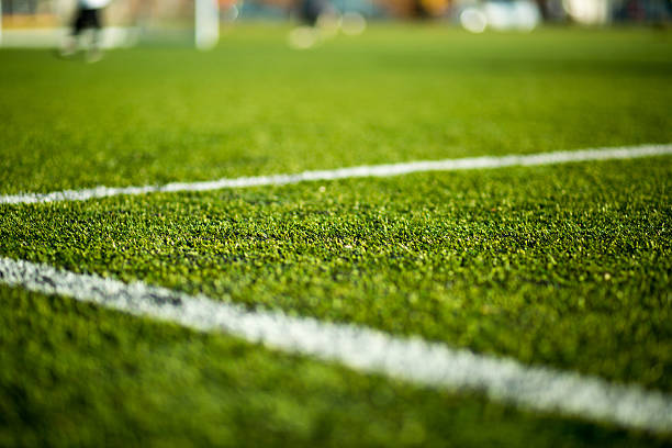 Soccer pitch Close-up of artificial turf. Blurred legs of soccer players in the background. turf stock pictures, royalty-free photos & images