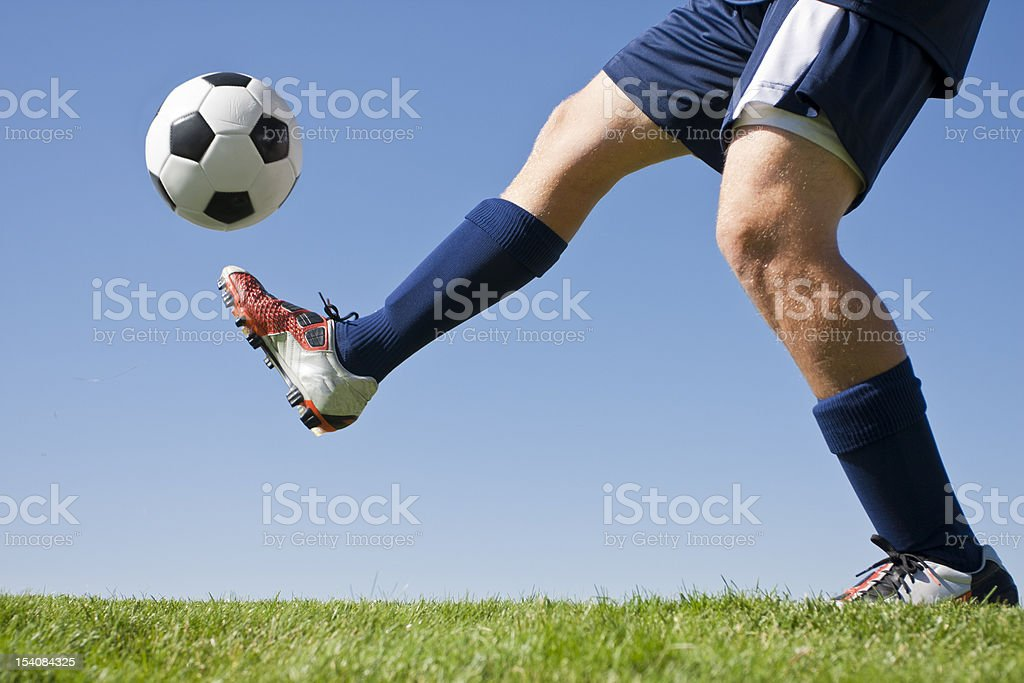 Soccer player and green grass kicking a soccer ball up stock photo