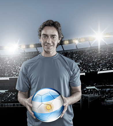 istock Soccer player Argentina holding ball with argentinian flag in stadium 928395122