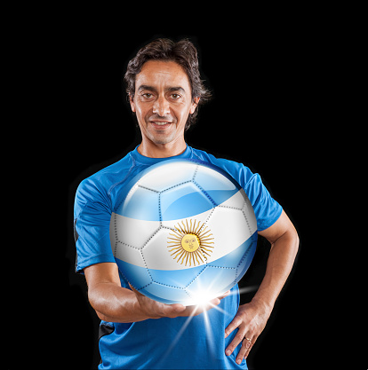istock Soccer player Argentina holding ball with argentinian flag isolated on black 928398840