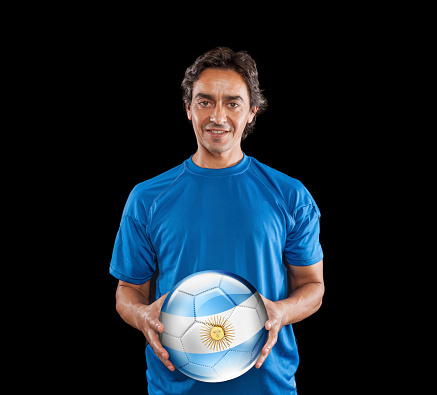 istock Soccer player Argentina holding ball with argentinian flag isolated on black 928399418