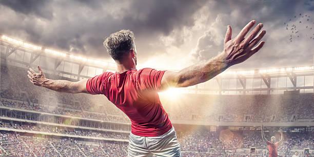 Soccer Player Arms Wide Celebrating After Scoring Goal in Match - foto de acervo