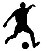 Soccer player as silhouette isolated while shooting a football
