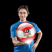 Soccer player Austria holding ball with austrian flag isolated on black