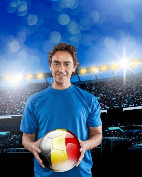 Soccer player Belgium holding ball with belgian flag in stadium stock photo