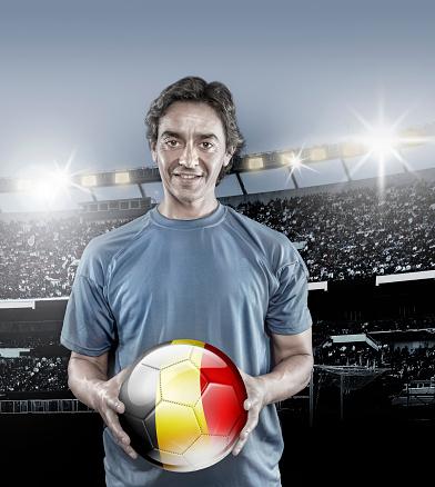 istock Soccer player Belgium holding ball with belgian flag in stadium 928722198