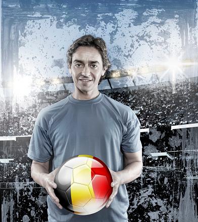 istock Soccer player Belgium holding ball with belgian flag in stadium 928724982