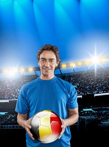 istock Soccer player Belgium holding ball with belgian flag in stadium 928726400