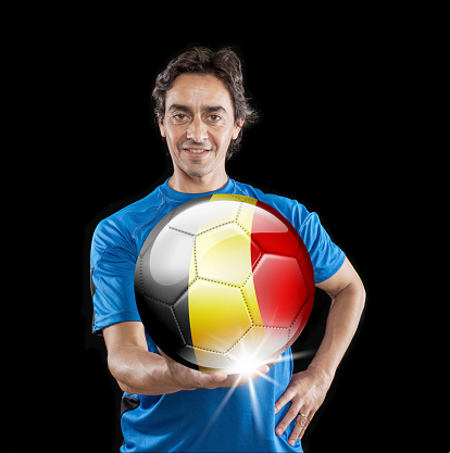 istock Soccer player Belgium holding ball with belgian flag isolated on black 928721938