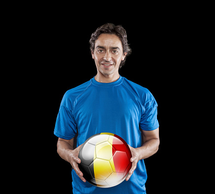 istock Soccer player Belgium holding ball with belgian flag isolated on black 928724476