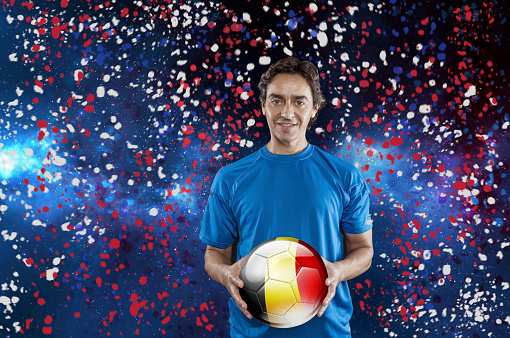 istock Soccer player Belgium holding ball with belgian flag under confetti 928721690