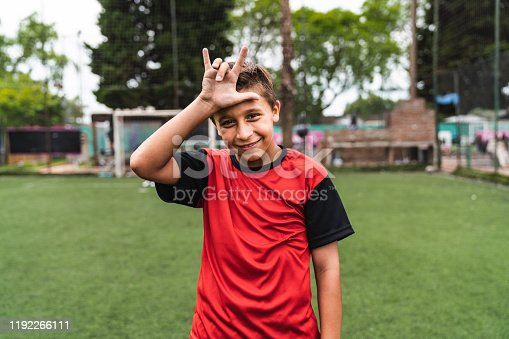 Soccer player boy doing hand gesture standing on a soccer field. He's celebrating. He's wearing red jersey.