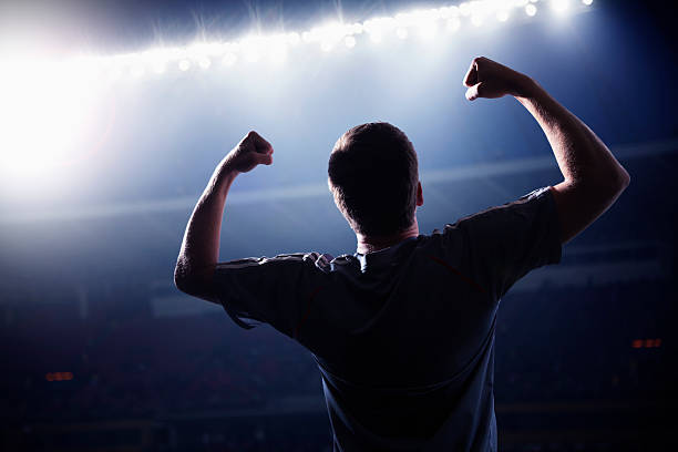 Soccer player cheering with his arms raised in the stadium stock photo