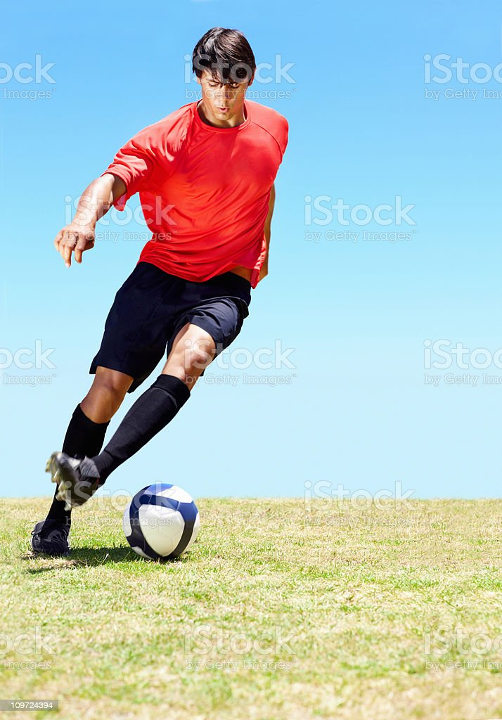 Soccer player dribbling a ball on the field royalty-free stock photo