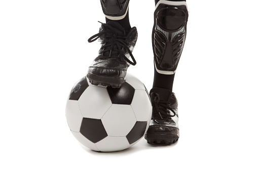 The feet of a soccer player with one of them resting on a soccer ball.