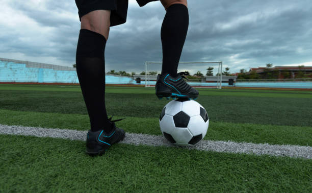 Soccer player foot on top of soccer ball stock photo