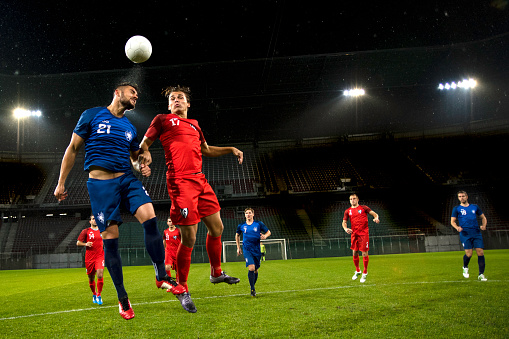 Soccer player in blue jersey in the air heading the ball. Stadium in the background.