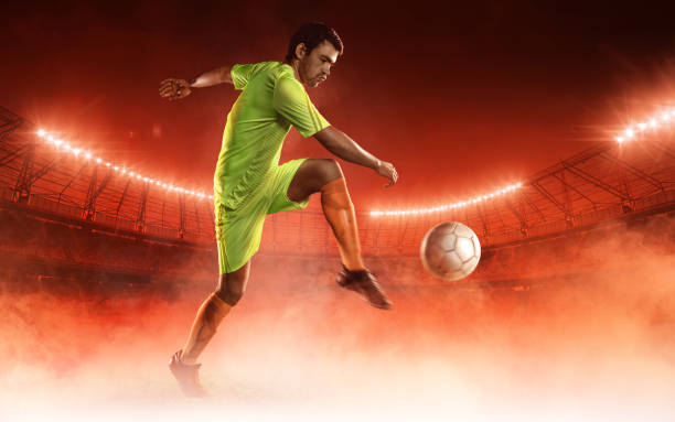 soccer player hits a ball on a soccer field - soccer competition stock photos and pictures