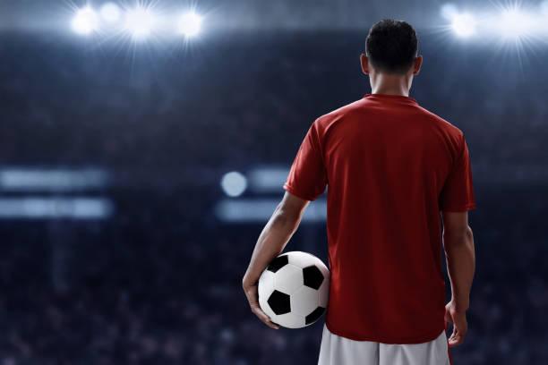 サッカー選手がサッカー ボールを保持しています。 - 背中 ストックフォトと画像