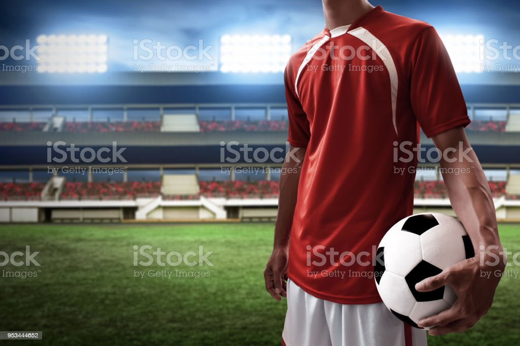 Soccer player holding soccer ball stock photo