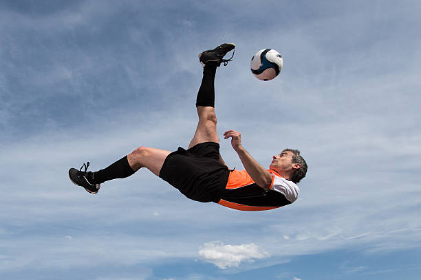 soccer player in a bicycle kick stock photo