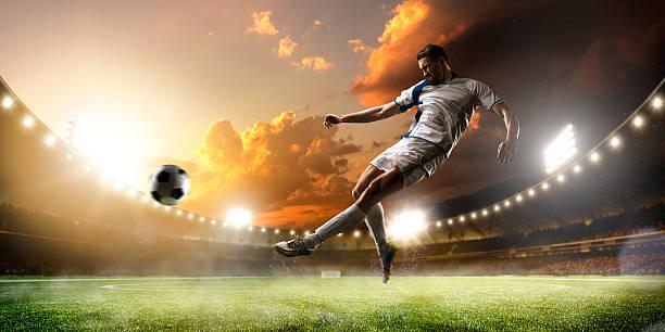 Fußballspieler in Aktion bei Sonnenuntergang panorama Hintergrund stadium – Foto