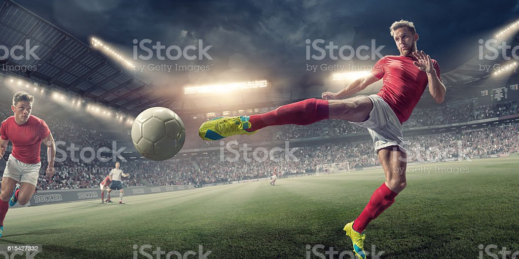 Soccer Player in Mid Air Volley Action During Football Match stock photo