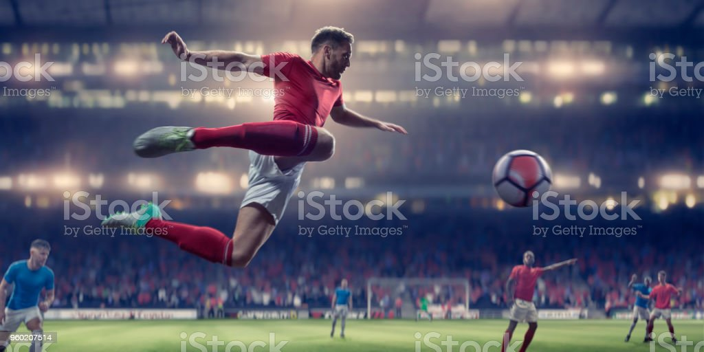 A professional male soccer in mid air with arms out and legs back,...