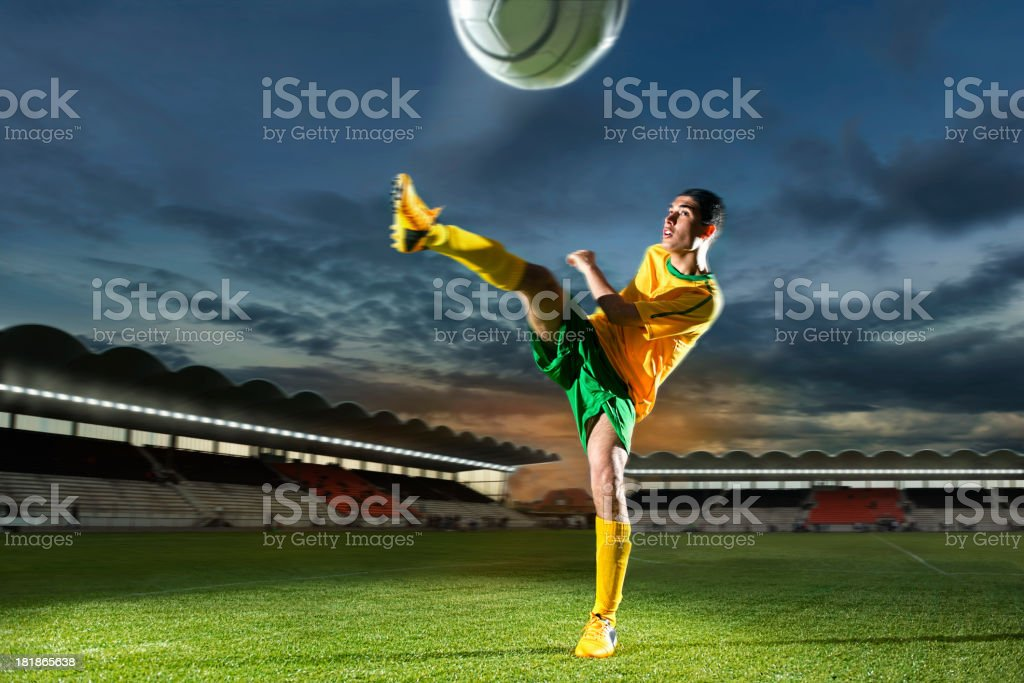 Soccer player is kicking the ball hard in stadium royalty-free stock photo