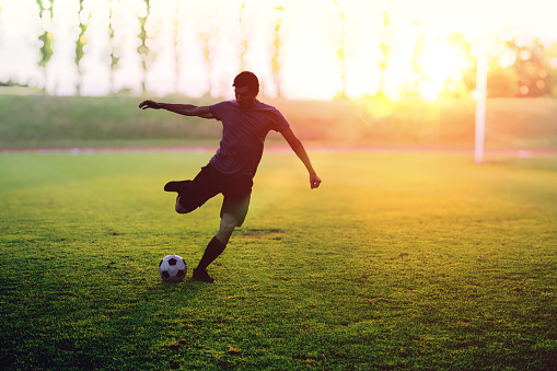istock Soccer player is shooting a ball in stadium at sunset. 831619558