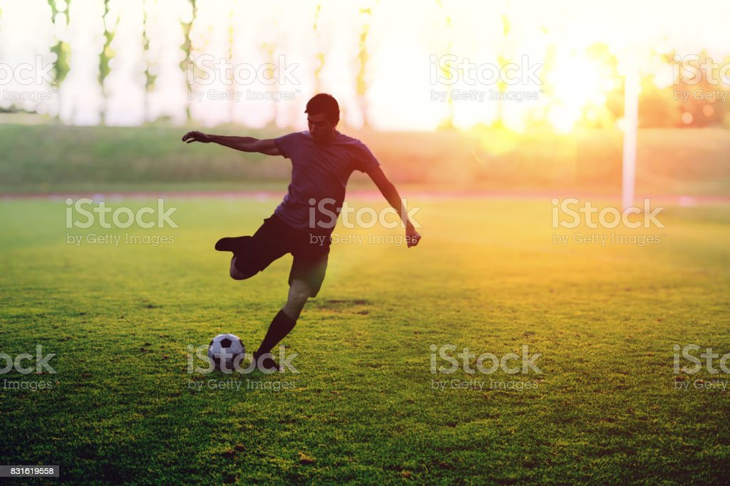Soccer player is shooting a ball in stadium at sunset. stock photo