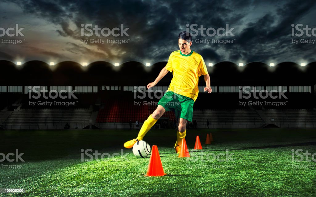 Soccer player is training with plastic cones at night stock photo