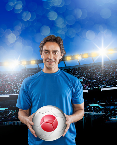 istock Soccer player Japan holding ball with japanese flag in stadium 929165732