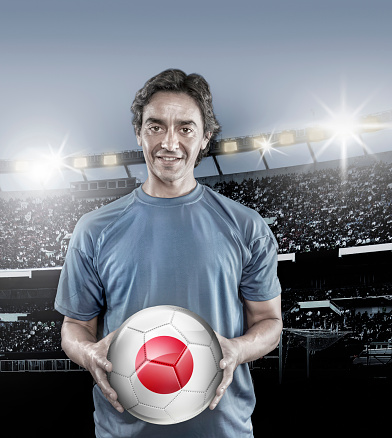 istock Soccer player Japan holding ball with japanese flag in stadium 929167998