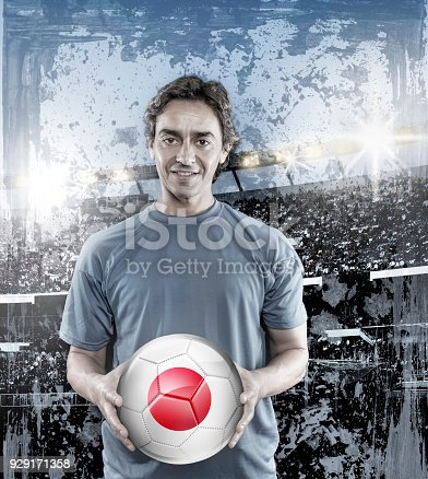 istock Soccer player Japan holding ball with japanese flag in stadium 929171358