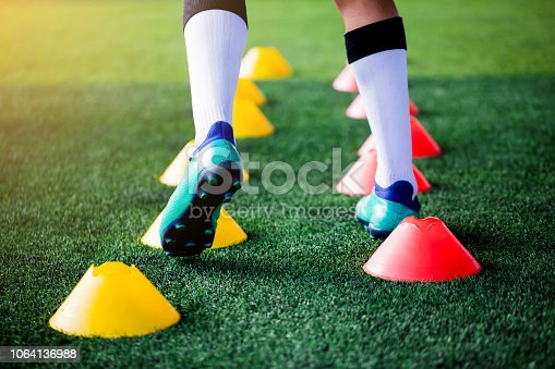 Soccer player Jogging and jump between cone markers on green artificial turf for soccer training. Football or Soccer Academy.