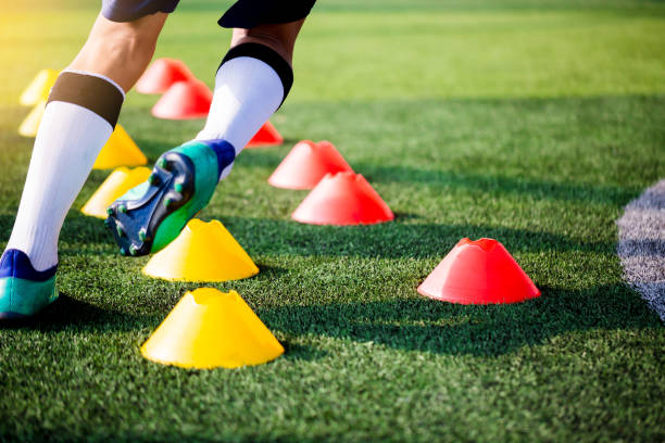Soccer player Jogging and jump between cone markers on green artificial turf for soccer training. Soccer player Jogging and jump between cone markers on green artificial turf for soccer training. Football or Soccer Academy. between stock pictures, royalty-free photos & images