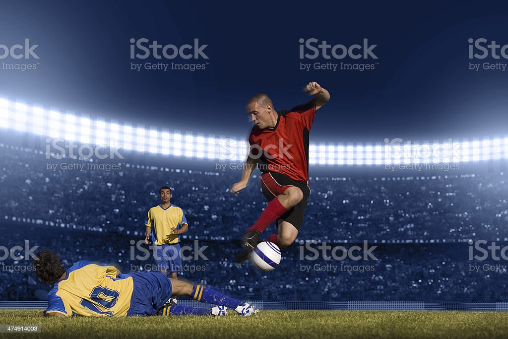 Soccer player jumping with ball stock photo