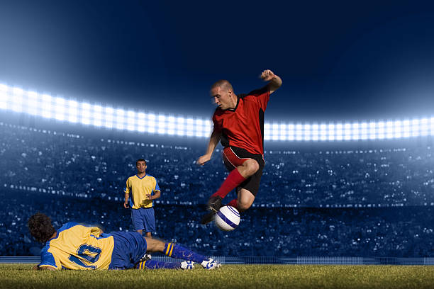 soccer player jumping with ball - soccer competition stock photos and pictures
